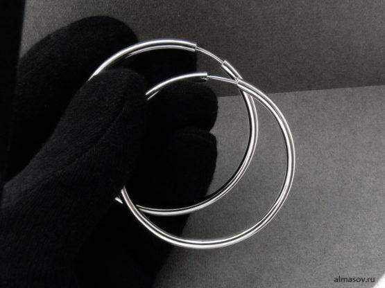 Большие круглые серебряные серьги кольца конго в руке