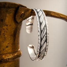 Узкий женский кубачинский серебряный браслет с чернью и гравировкой в виде листьев, на ручке кувшина.