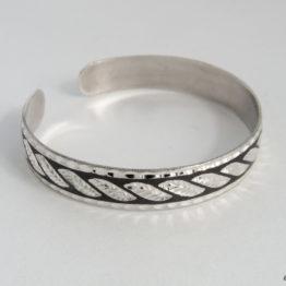Узкий женский кубачинский серебряный браслет с чернью и гравировкой в виде листьев.